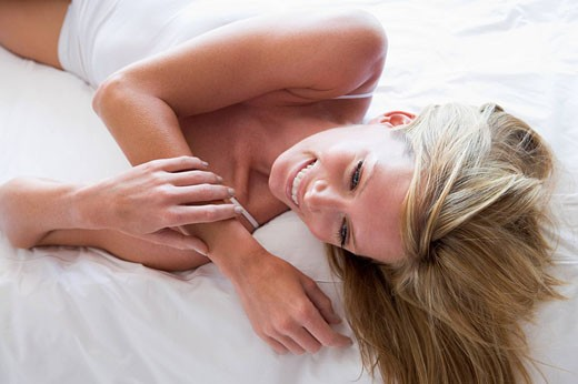 Stock Photo: 1888R-14755 Woman lying in bed smiling