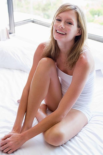 Woman sitting on bed smiling : Stock Photo