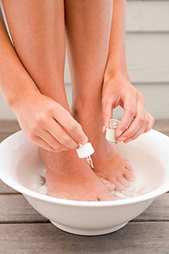 Woman giving herself pedicure : Stock Photo