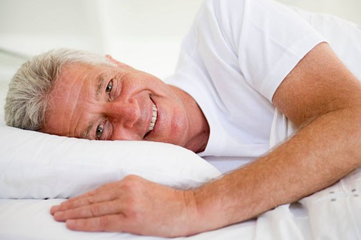 Man lying in bed smiling : Stock Photo
