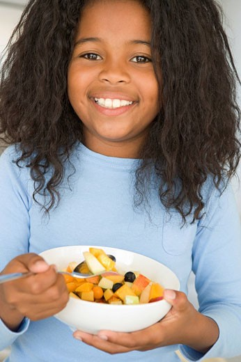 Young girl in kitchen eating bowl of fruit smiling : Stock Photo