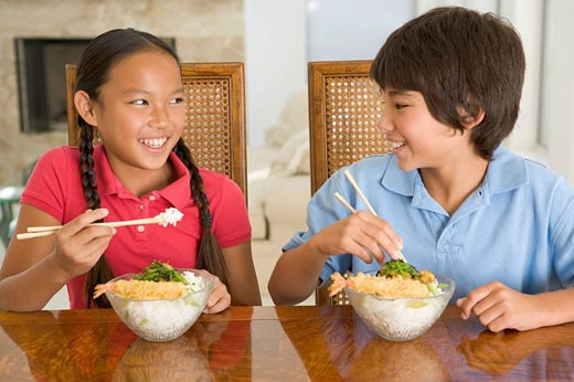 Two young children eating Chinese food in dining room smiling : Stock Photo