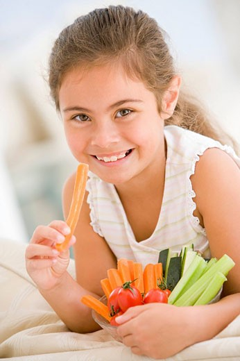 Young girl eating bowl of vegetables in living room smiling : Stock Photo