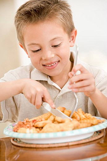 Young boy indoors eating fish and chips smiling : Stock Photo