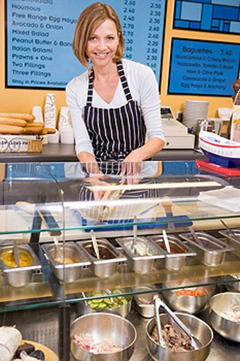 Woman standing at counter in restaurant smiling : Stock Photo