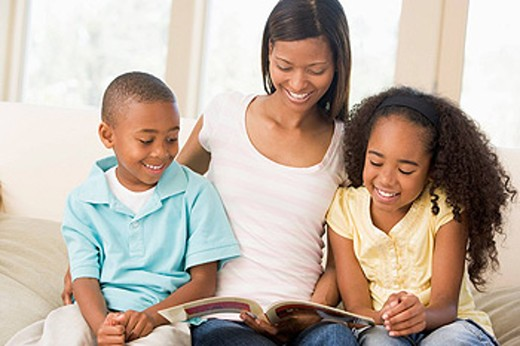 Woman and two children sitting in living room reading book and smiling : Stock Photo