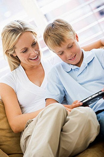 Stock Photo: 1888R-16026 Woman and young boy in living room with handheld video game smiling