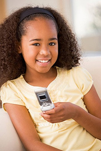 Stock Photo: 1888R-16049 Young girl in living room using cellular phone and smiling