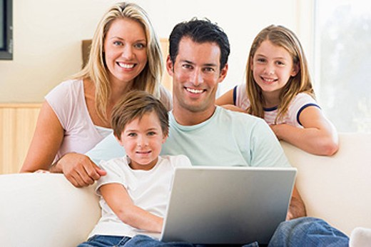 Family in living room with laptop smiling : Stock Photo