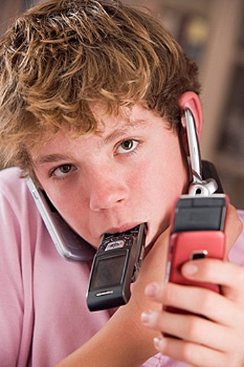 Young boy in bedroom holding many cellular phones : Stock Photo