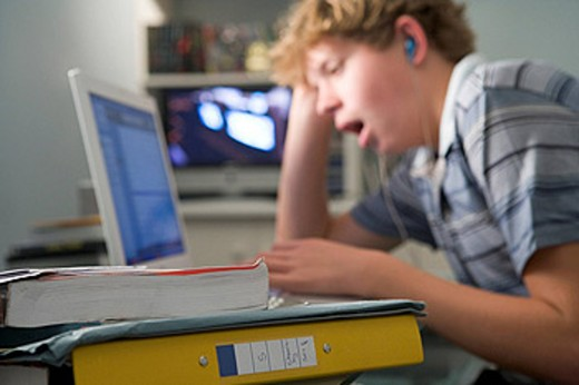 Stock Photo: 1888R-16136 Young boy in bedroom yawning using laptop and listening to MP3 player