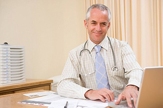 Stock Photo: 1888R-16214 Doctor using laptop in doctor´s office smiling