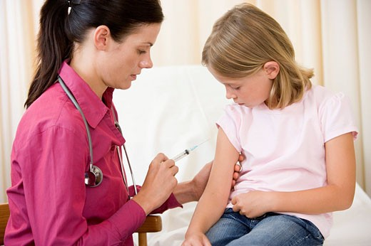 Stock Photo: 1888R-16231 Doctor giving needle to young girl in exam room