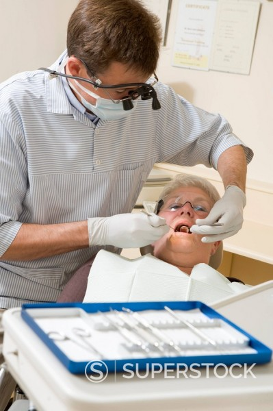 Stock Photo: 1888R-16282 Dentist in exam room with woman in chair
