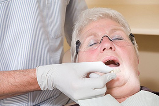 Dentist in exam room fitting dentures on woman in chair : Stock Photo
