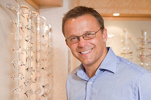Man trying on eyeglasses at optometrists smiling : Stock Photo