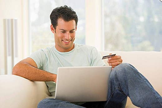 Man in living room using laptop and holding credit card smiling : Stock Photo