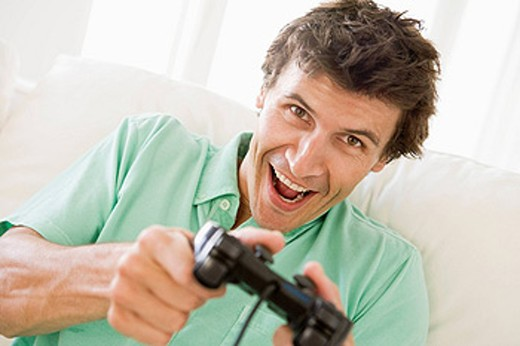 Stock Photo: 1888R-16362 Man in living room playing videogames smiling