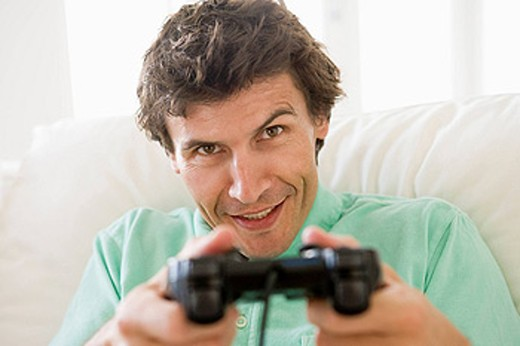 Man in living room playing videogames smiling : Stock Photo