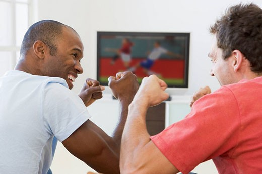 Two men in living room watching television and cheering : Stock Photo