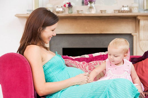 Pregnant mother with daughter in living room touching belly and smiling : Stock Photo