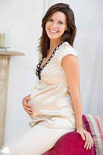 Pregnant woman sitting in living room smiling : Stock Photo