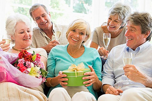 Five friends with champagne and gifts in living room smiling : Stock Photo