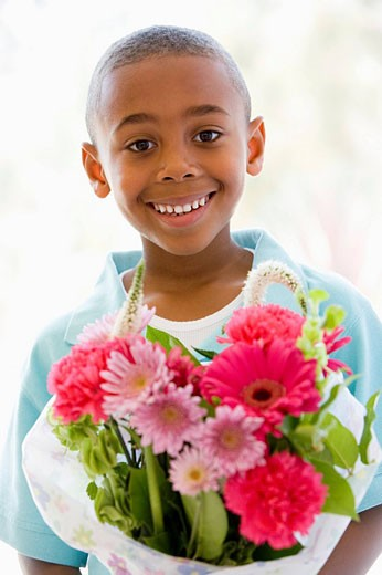 Stock Photo: 1888R-17293 Young boy holding flowers smiling