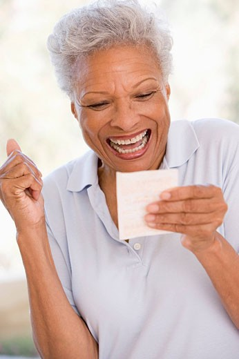 Woman with winning lottery ticket excited and smiling : Stock Photo
