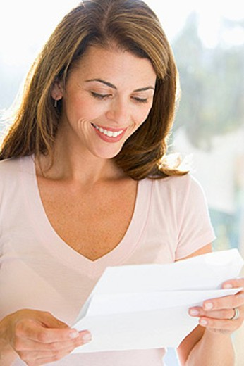 Woman reading letter smiling : Stock Photo