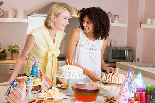 Two women at party getting sandwiches smiling : Stock Photo