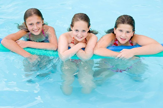 Stock Photo: 1888R-17682 Three young girl friends in swimming pool with pool noodle smiling