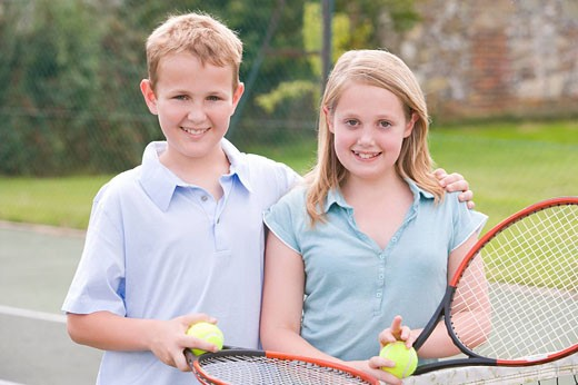 Two young friends with rackets on tennis court smiling : Stock Photo
