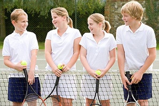 Four young friends with rackets on tennis court smiling : Stock Photo