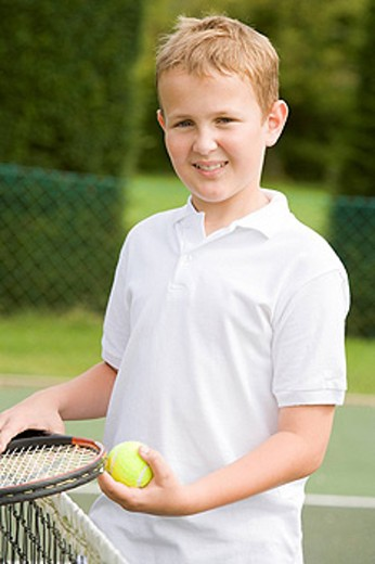 Young boy with racket on tennis court smiling : Stock Photo