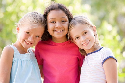 Three young girl friends standing outdoors smiling : Stock Photo