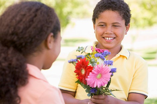 Young boy giving young girl flowers and smiling : Stock Photo