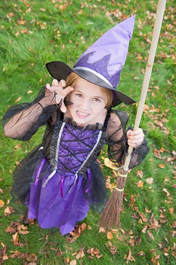 Young girl outdoors in witch costume on Halloween : Stock Photo