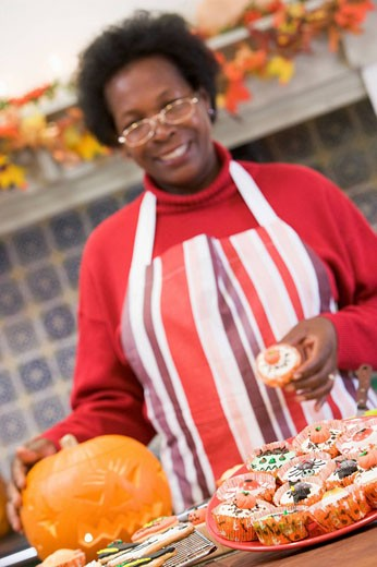 Woman in kitchen making Halloween treats and smiling : Stock Photo