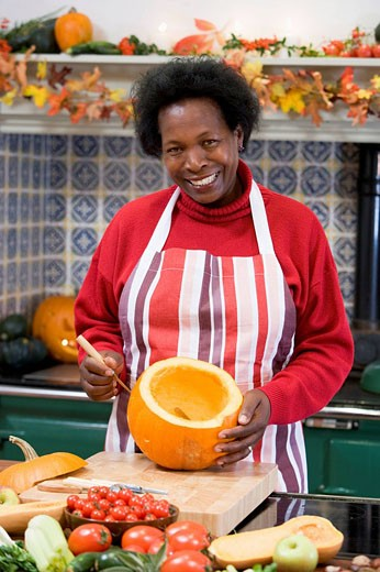 Woman on Halloween making jack o lantern smiling : Stock Photo