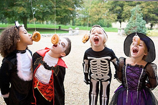 Four young friends on Halloween in costumes eating donuts hanging off strings : Stock Photo