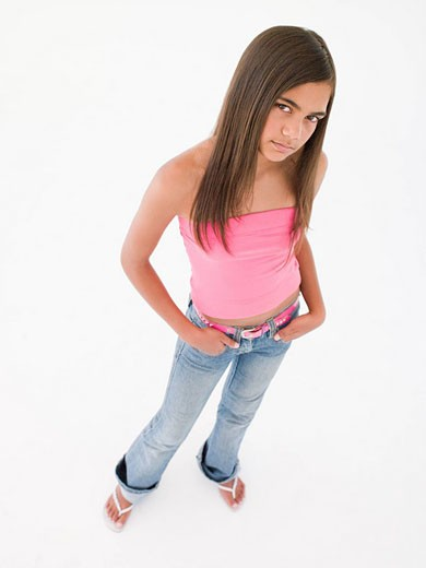 Stock Photo: 1888R-17960 Young girl standing with hands in pockets frowning