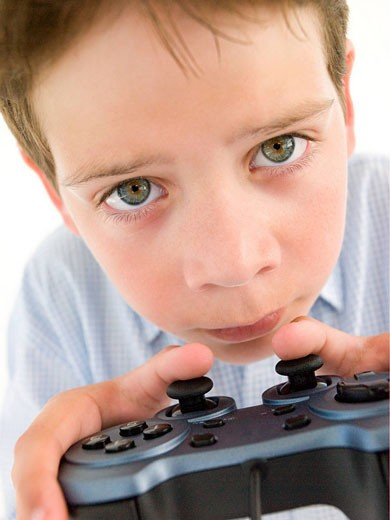 Stock Photo: 1888R-18084 Young boy using videogame controller and concentrating
