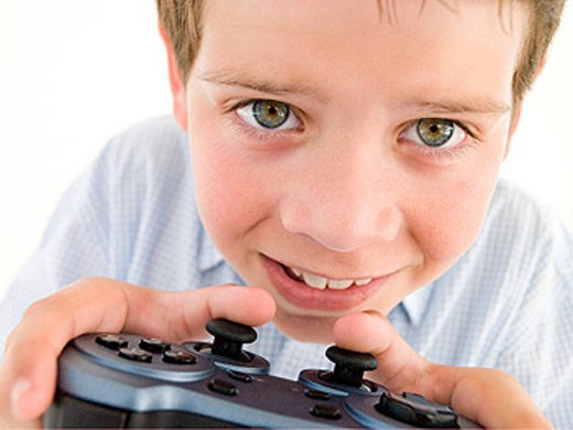 Young boy using videogame controller smiling : Stock Photo