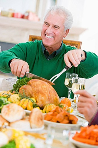 Man Carving Up Turkey At Christmas Dinner : Stock Photo