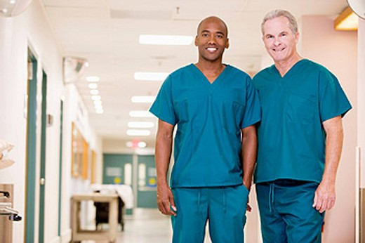 Stock Photo: 1888R-18942 Two Orderlies Standing In A Hospital Corridor