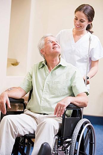 Nurse Pushing Man In Wheelchair : Stock Photo