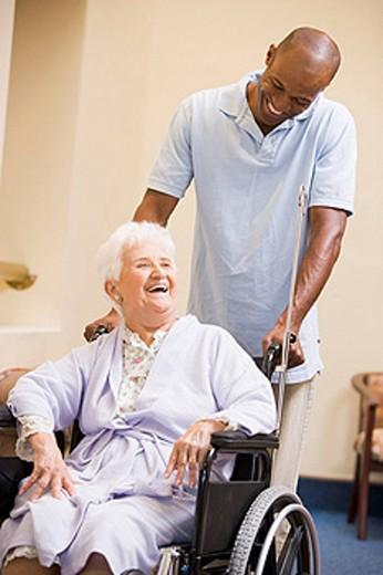 Nurse Pushing Senior Woman In Wheelchair : Stock Photo