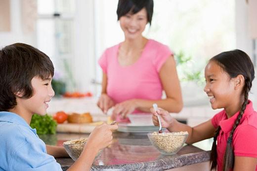 Stock Photo: 1888R-20139 Children Enjoying Breakfast While Mother Is Preparing Food