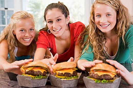 Teenage Girls Eating Burgers : Stock Photo